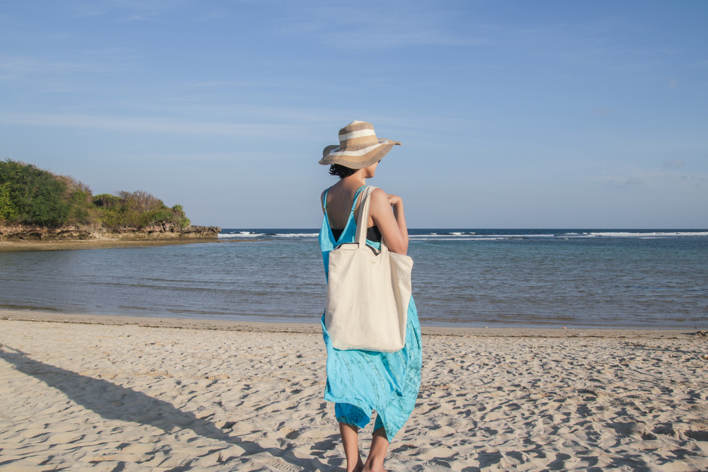 Woman with tote bag on beach